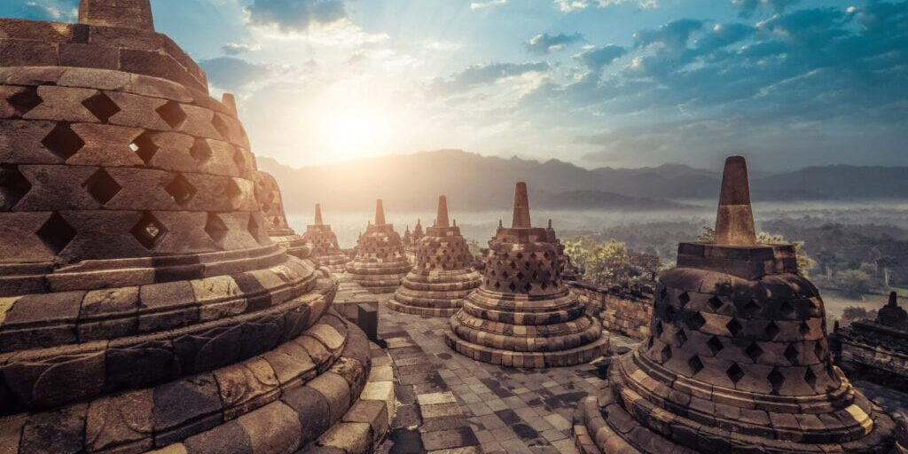 Amazing view of stone stupas at ancient Borobudur Buddhist temple against beautiful landscape on background. Great religious architecture. Magelang, Central Java, Indonesia